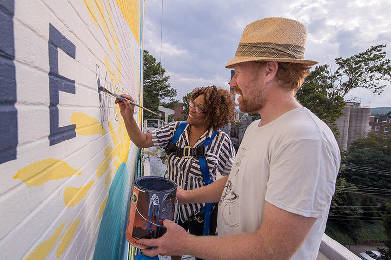Poet Rita Dove helps muralist David Guinn add the finishing touches to their mural on the Graduate Hotel in Charlottesville.