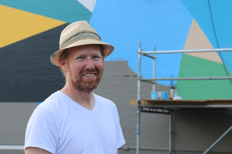 "Philadelphia artist David Guinn stands in front of the main face of his mural on the Graduate Hotel in Charlottesville. The mural was inspired by Rita Dove's poem ""Testimonial."""