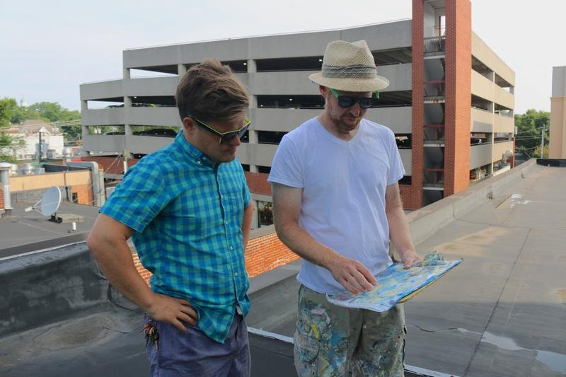 Ross McDermott, the outgoing head of the Charlottesville Mural Project, reviews the mural design print with artist David Guinn.