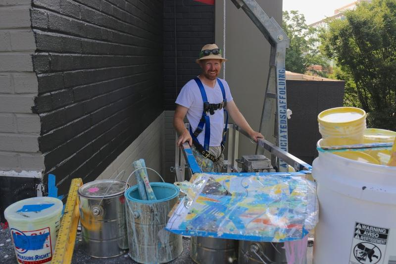 Artist David Guinn prepares to load paint cans on the swing stage.