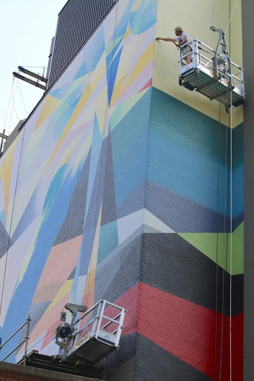 Artist David Guinn paints high up on the swing stage. The mural wraps around the corner of the Graduate Hotel.