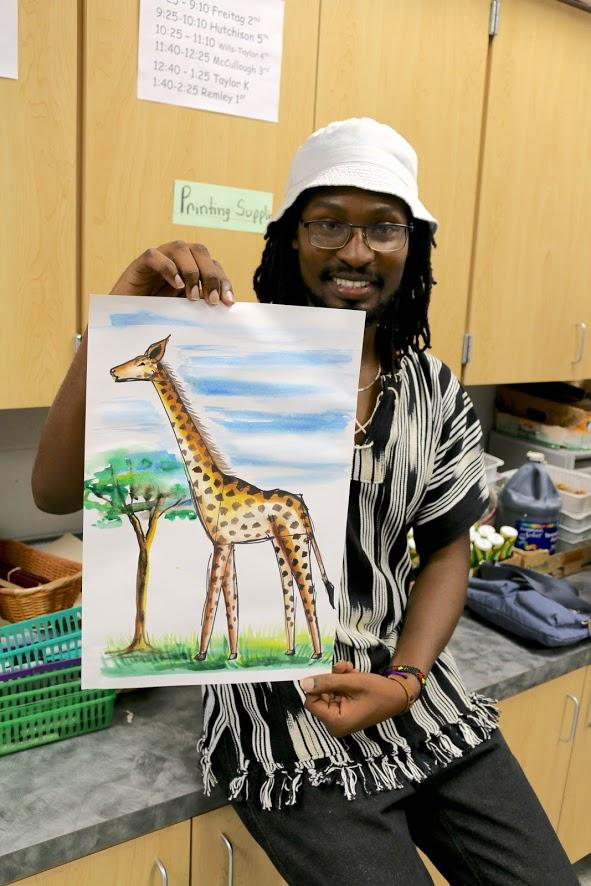 At the end of class, Figy shows off his giraffe painting.