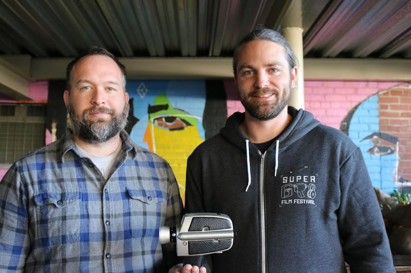 Tim Estep and Paul Somers, co-founders of the SuperGR8 Film Festival, pose with one of the Super 8 cameras they lend out to festival participants.
