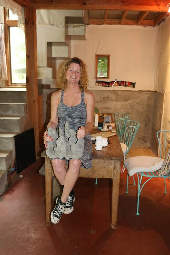 Evelyn Tickle, founder of Grow Oyster Reefs, holds a concrete reef restoration tile in her lap. Around her, you can see the concrete walls, floor and stairs that she installed as part of an addition to her 19th century home in Charlottesville.