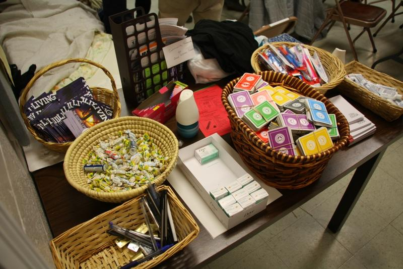 A table full of free items welcomes homeless men to First Presbyterian Church, including: cough drops, playing cards, pens, soap, toothbrushes, and plastic bags.