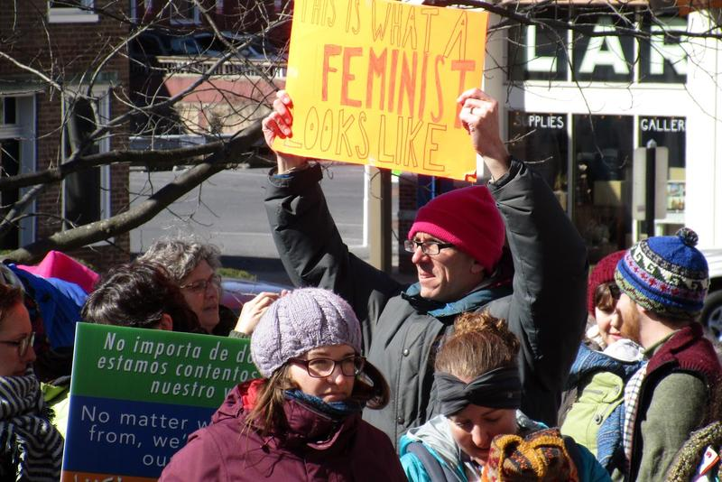"A participant at the rally holds a sign stating, ""This is what a feminist looks like."""