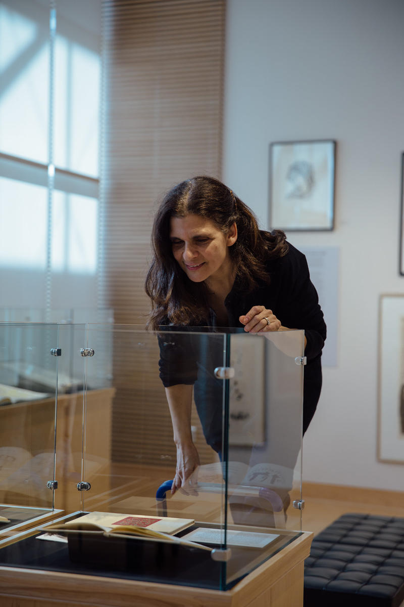 Guest Curator Laura Katzman installs a display case in the exhibition, Drawing on the Left.