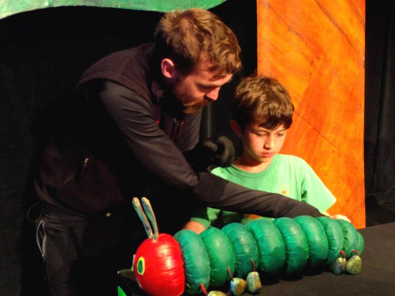 Graeme Black Robinson helps a child get hold of the caterpillar puppet.