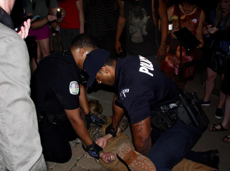 Police arrest a man who was supporting efforts to remove the Lee statue.