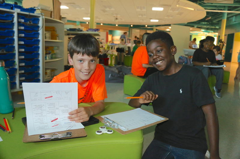Fifth grader Ian Scott (left) collaborates with a friend on a task sheet.