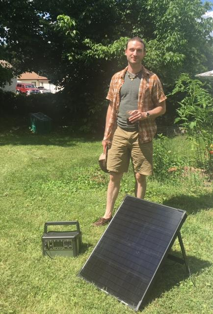 Cook stands in his backyard next to his energy supply: three solar panels and a sun-charged battery.