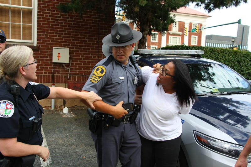 A Charlottesville Police officer intervenes for the safety of a protester as a Virginia State Police officer arrests the protester.