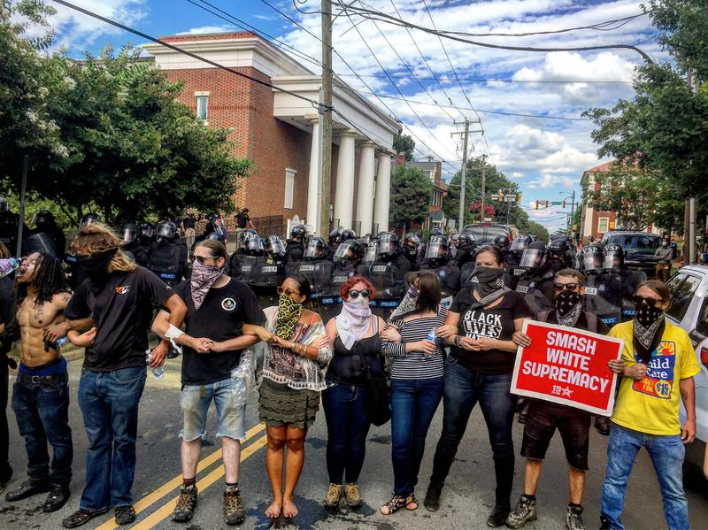 Protesters link arms at the July 8th rally of the Ku Klux Klan in Charlottesville. City officials are hoping for a more peaceable rally on Saturday, August 12th as hundreds of alt-right activists are expected to demonstrate.