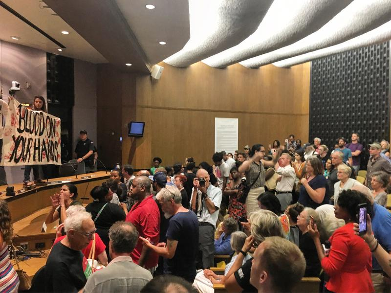 More than 150 people packed into Charlottesville City Council chambers on Monday night. Two activists jumped on the dais as councilors left the chamber.