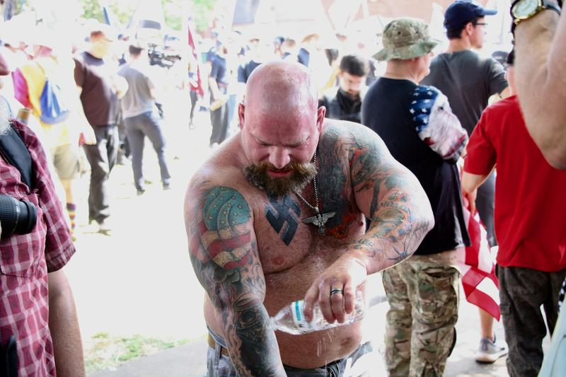 A Neo Nazi washes his skin and flushes his face with water after getting sprayed by pepper spray from a counter protester.