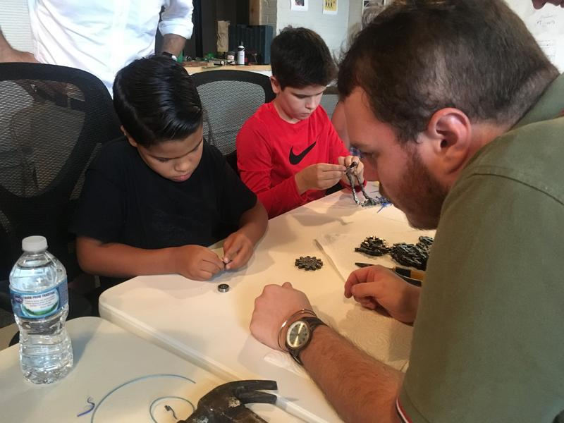 Makerspace member Andy Martin works with Asher Wells, 7, and Stephen Wells, 11, to create a do-it-yourself fidget spinner.