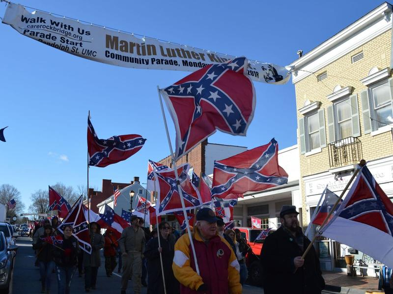 A sign above Lee-Jackson Day marchers advertised for the Martin Luther King Jr. Day parade, two days later.