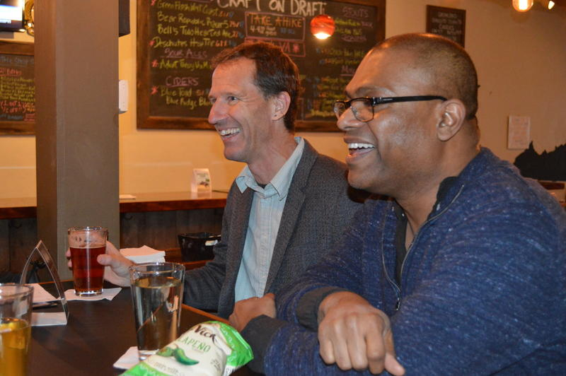 Chris Gavaler, an English professor at Washington and Lee University, and Atin Basu, an economics professor at Virginia Military Institute, share a laugh over beers at the weekly Rockbridge Civil Discourse meeting.