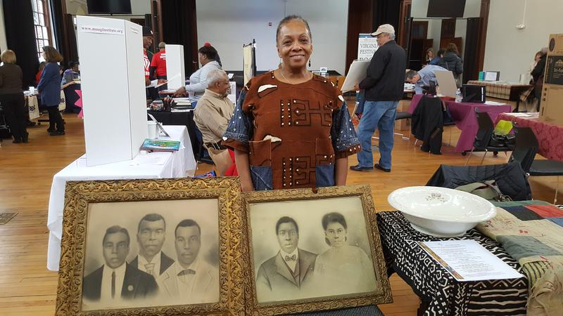 Lillie Williams showcases her family treasures: the portraits of her grand-uncles and her grandparents, and a large hollow dish and quilt from her grandmother.