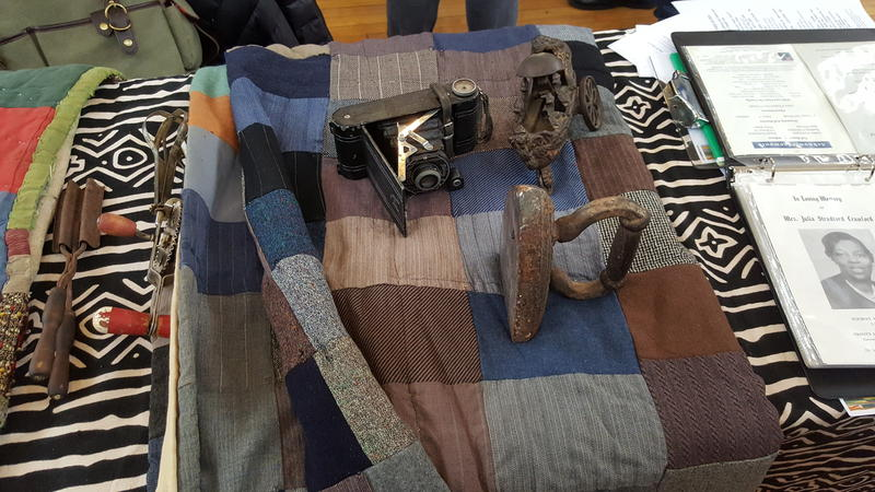 Ruby Boston's family artifacts (from left to right): a crimping iron and a hand blender, a camera and boat toy over a hundred years old, and an iron - all laid out on a quilt from her grandparents.