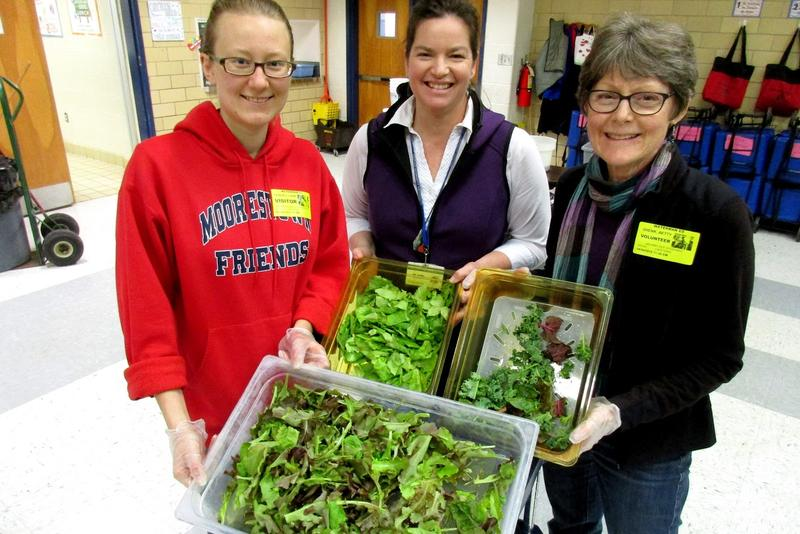Kathy Yoder (center) is a special education assistant and the garden coordinator at Waterman Elementary School, shown here in the cafeteria with volunteers Liana Hershey (left) and Betty Shenk, who are serving fresh-picked greens for students to taste.