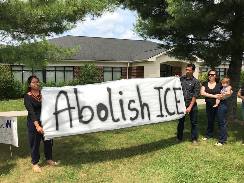 Karina Vasquez (left) and Boris Ozuna hold a banner in front of the Harrisonburg ICE office.