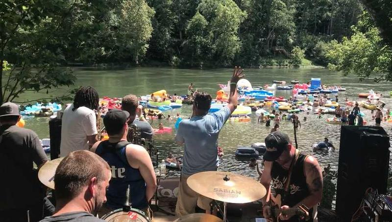 Bands perform on a stage facing frolickers in the Shenandoah River at Doah Fest in Luray.
