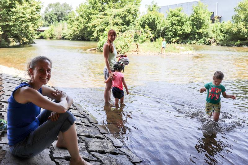 Karen Brookshire, her friend Bethany Persian and their kids relax under a bridge over the South River at Constitution Park in Waynesboro.