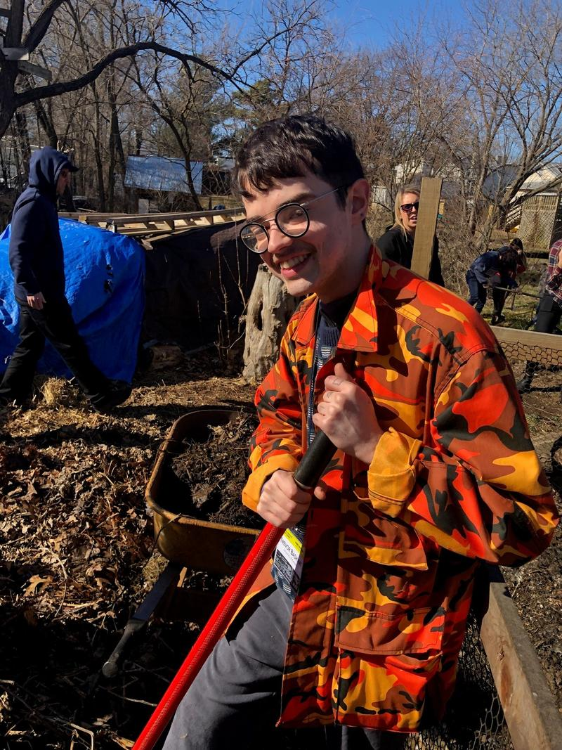University of Kansas student Trevor Bashaw digs compost as part of a field experience during the summit.