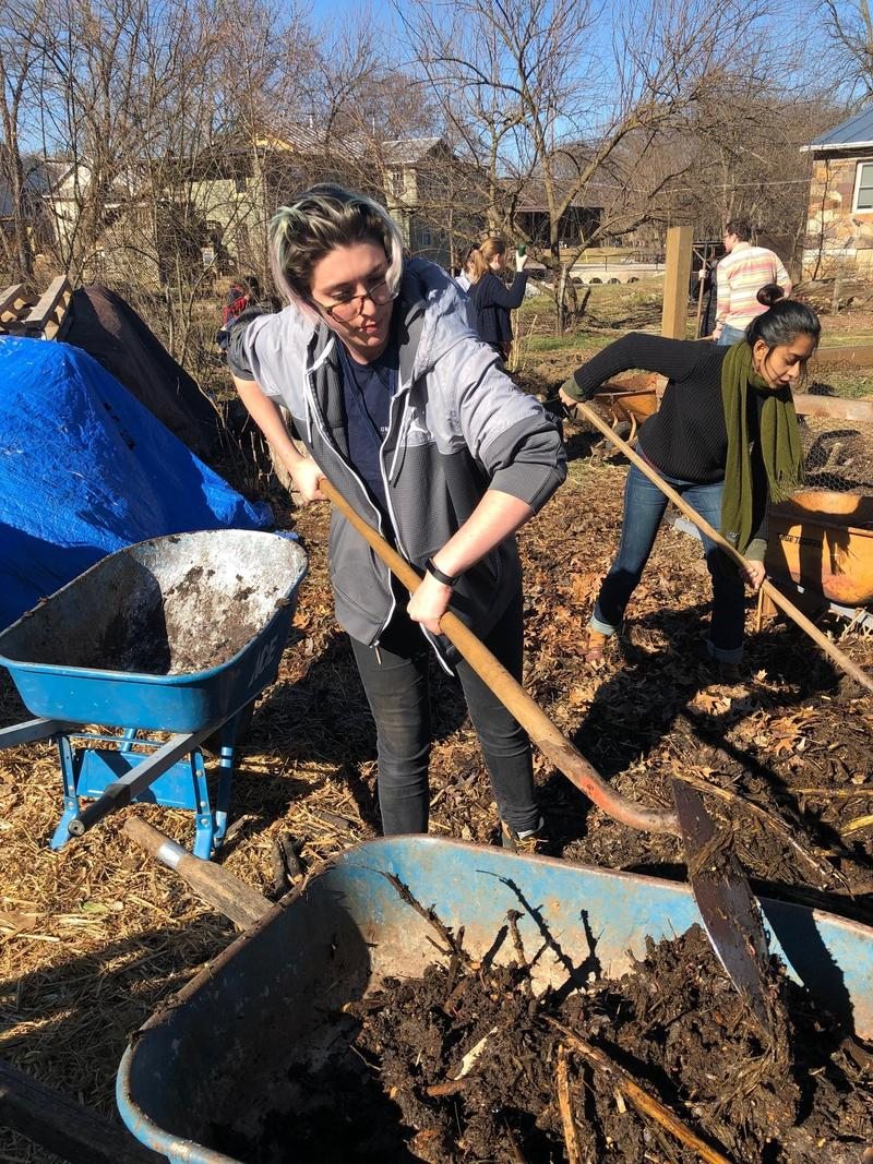 JMU student Alexandria Shafer digs compost as part of a field experience during the Emerging Creatives Summit at JMU.