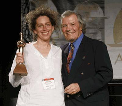 Sarah Cohen of Route 11 Potato Chips holds her award as Jacques Pépin stands by.