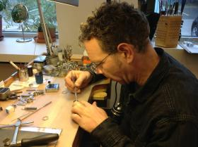 Daniel Juzwiak arranges a diamond on a stainless steel ring.