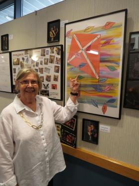 Barbara Jones pointing out the art kite she made with Cristina Bryant
