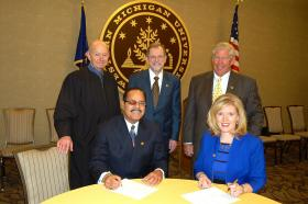 Trustees Crumm and Ronald Hall are seated at the table with Judge William G. Schma, President Dunn and Board Chair William Johnston