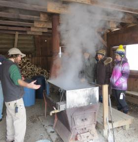 Brown and the tour group stand in front of the Nature Center's 40 gallon evaporator they use to boil the sap into syrup.