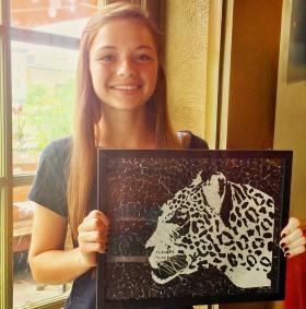 Artist Paige Harrison with one of her collage portraits.