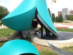 WMU alum and artist Ricardo de Sousa Costa repairing 'The Thunderer'