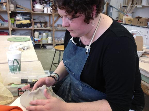 Jen Lawson-Steeves works on one of her moon-like masks at the Kalamazoo Institute of Arts studio.