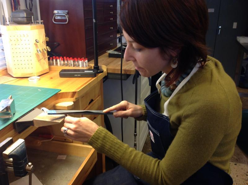 Kara Aubin filing down a metal pendant.