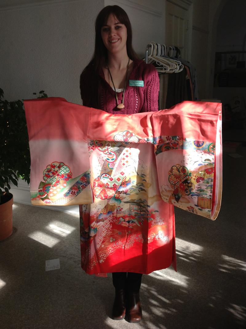 Warner-Talcott holds a kimono that a girl might wear to celebrate her 7th birthday.