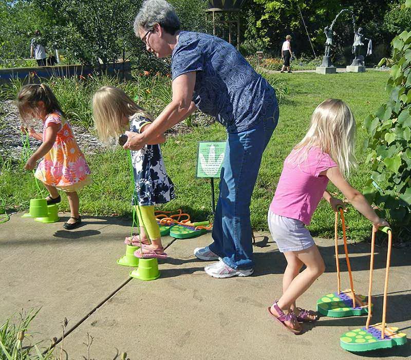 Some children practice walking like Dinosaurs at Leila Arboretum's Children's Garden in Battle Creek