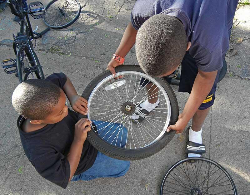 Two boys grab a tire at the Fixapalooza workshop