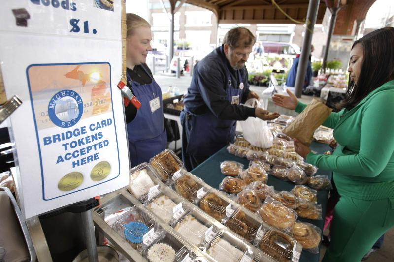 Temeka Williams, right, of Detroit, uses her Bridge card tokens at the Farmer's Market in Detroit in 2010.