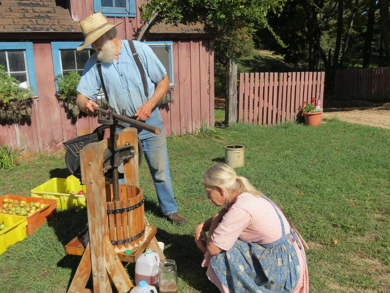 Joan Donaldson makes sure the cider goes in the jug while her husband John turns the crank of the cider press