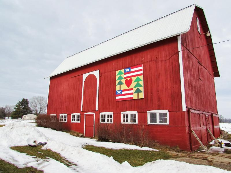"This barn quilt, titled ""Love The Land,"" is framed on a structure that is over 100 years old."