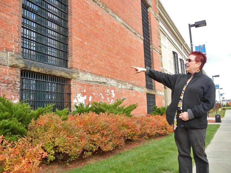 Judy Gail Krasnow in front of apartments with bars on windows.