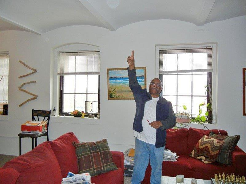 Louis Cubille in his apartment pointing to the ceiling of the old prison cells