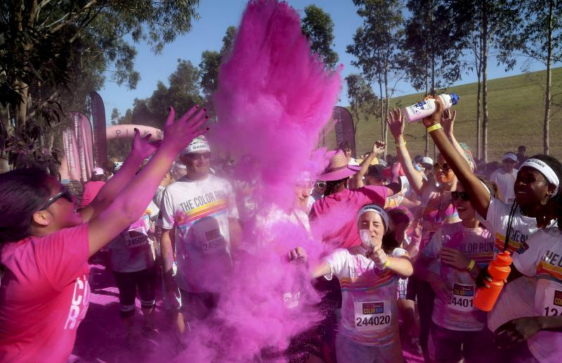 Pink powder is thrown up as people run through a color station during the Color Run in Sydney, Australia, Sunday, Feb. 9, 2014.  The event is coming to Kalamazoo on April 12.