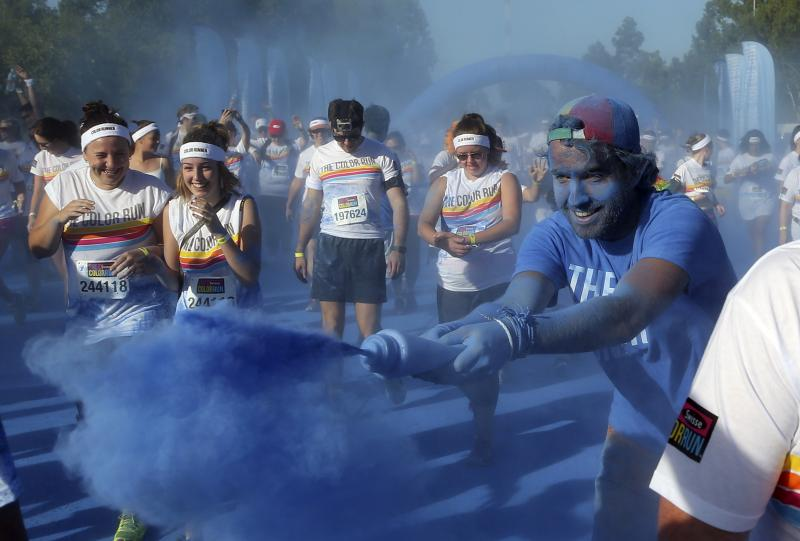 People run through the blue color station during the Color Run in Sydney, Australia, Sunday, Feb. 9, 2014.