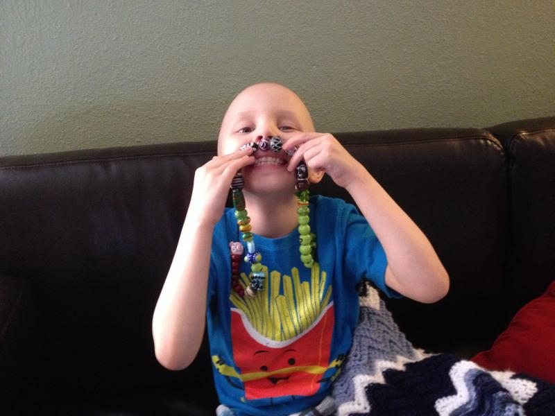 7-year-old Maddux Hescock plays with his Journey Beads from Bronson Hospital